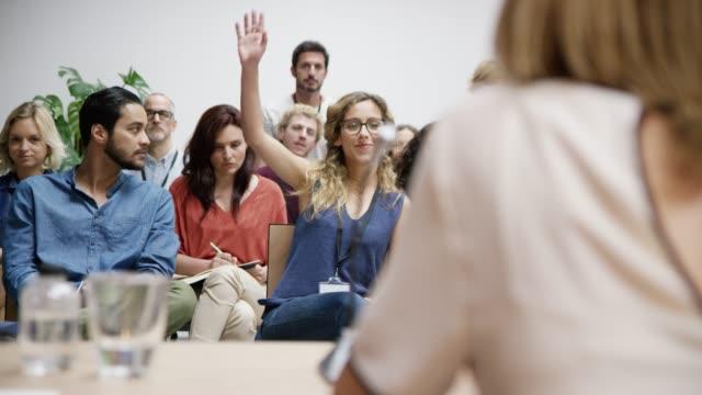 vídeos de stock e filmes b-roll de businesswoman raising hand at networking event - orador público