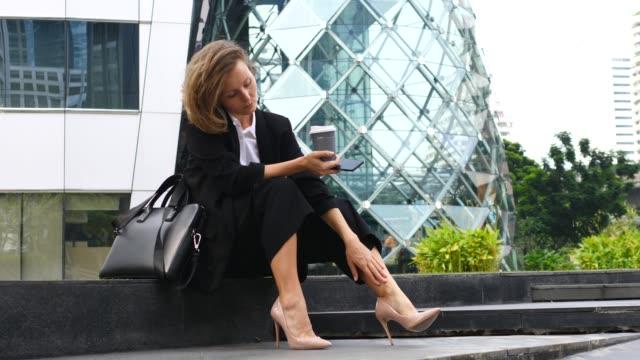 geschäftsfrau ruht mit kaffee im freien gefühl schmerzen nach dem tragen high heels - formelle geschäftskleidung stock-videos und b-roll-filmmaterial