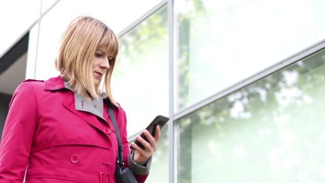 Businesswoman sending sms text message at outdoor