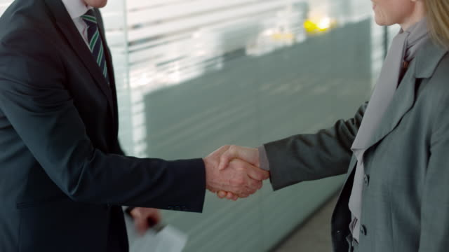 Businesswoman shaking hands with a male colleague in the hallway video