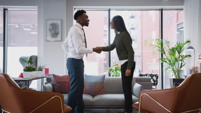 Businesswoman Shaking Hands With Male Interview Candidate In Seating Area Of Modern Office Businesswoman meeting male job candidate in seating area of modern office and shaking hands - shot in slow motion job interview stock videos & royalty-free footage