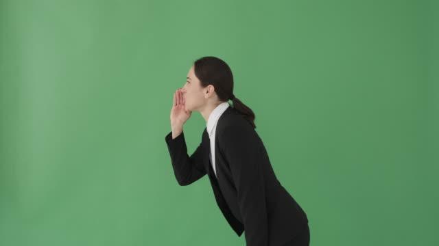 Businesswoman sharing a secret over green screen