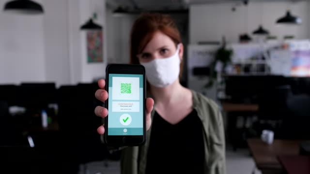 vidéos et rushes de femme d'affaires affichant l'application de suivi de virus de corona sur son téléphone - montrer