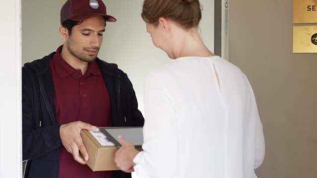 女商人在數位平板電腦上簽名包裹 - postal worker 個影片檔及 b 捲影像