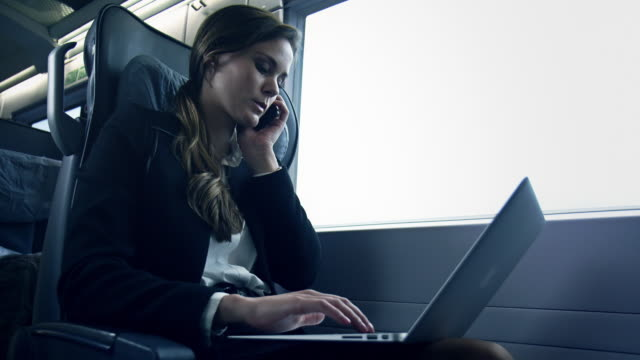 donna d'affari seduto e lavorando in treno - direttrice video stock e b–roll