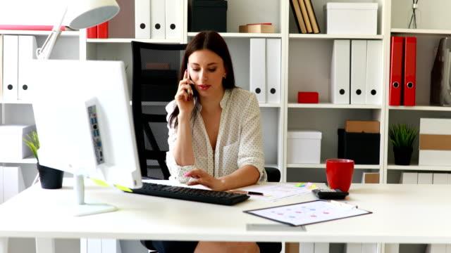 affärskvinna som sitter i office-stol prata telefon - looking inside inside cabinet bildbanksvideor och videomaterial från bakom kulisserna