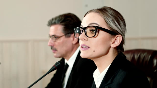 businesswoman speaker answers the journalists questions on press conference. - conferenza stampa video stock e b–roll