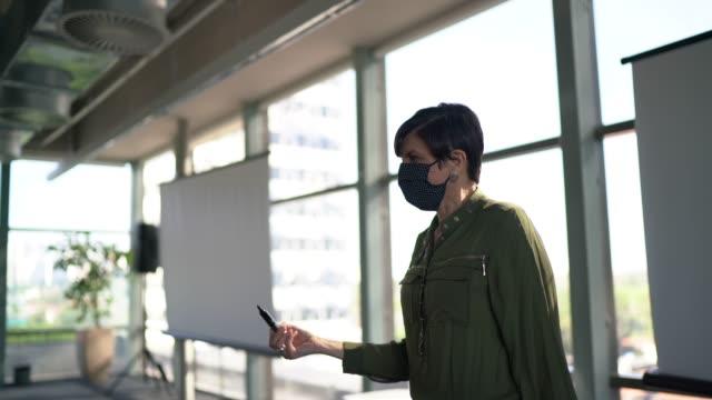 vídeos de stock e filmes b-roll de businesswoman speaking at a business conference - with face mask - orador público