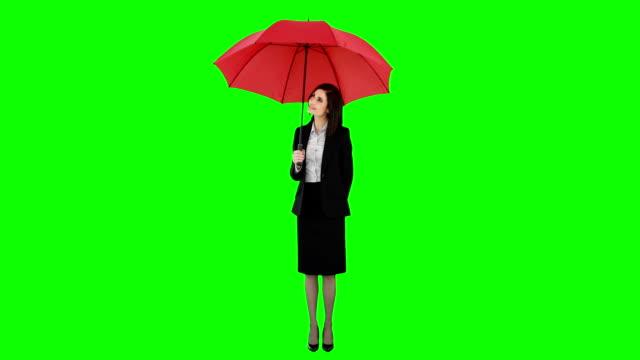 Businesswoman standing under umbrella