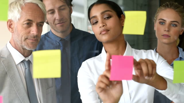 Businesswoman sticking sticky notes video