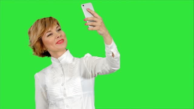 Zakenvrouw grappige selfie met telefoon op te nemen op een groen scherm, Chromakey video