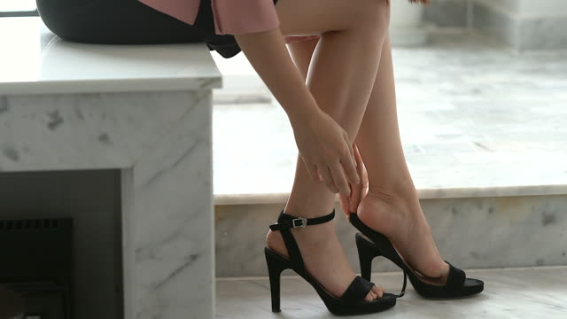 Businesswoman taking on high heels shoes before go to work.