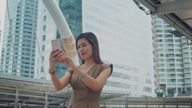 Businesswoman taking selfie on footbridge video