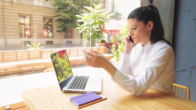 donna d'affari parlando al cellulare. - owner laptop smartphone video stock e b–roll