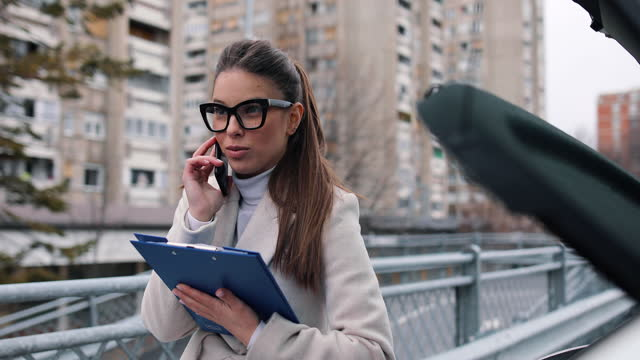 Businesswoman talking on a cell phone in the parking lot in front of her car. He holds business documents in his hands and pulls them out of the trunk video