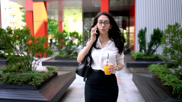 Businesswoman talking on her phone Young beautiful businesswoman holding fresh orange juice and talking on her phone office park stock videos & royalty-free footage