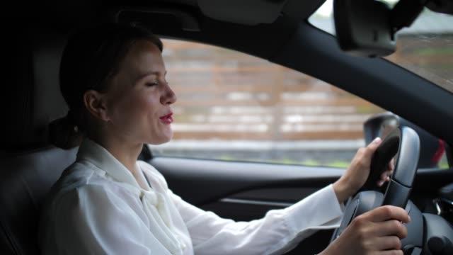 businesswoman talking on in-car speakerphone - autista mestiere video stock e b–roll