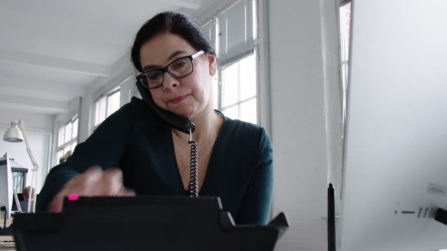 Businesswoman talking on landline phone from her desk Mature woman working at her desk making a phone call with office intercom and looking at computer screen. Businesswoman talking on landline phone while working at her office desk. landline phone stock videos & royalty-free footage