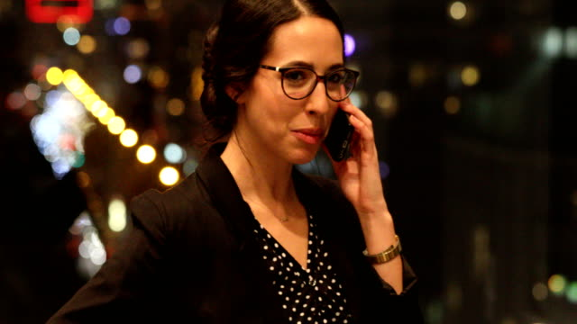 Businesswoman talking on mobile phone by office window video