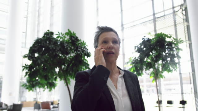 Businesswoman talking on mobile phone in the lobby at office 4k