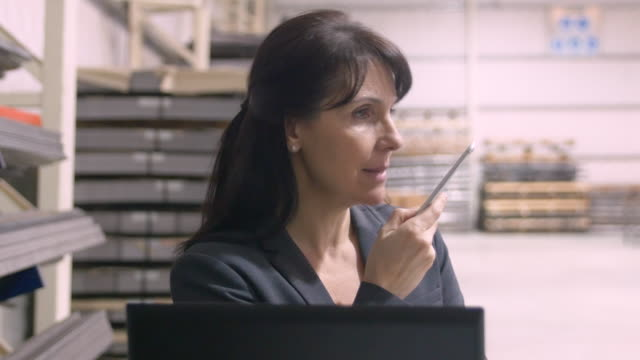 Businesswoman talking on mobile phone in warehouse video