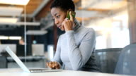 istock Businesswoman talking on phone while using laptop 1085386094