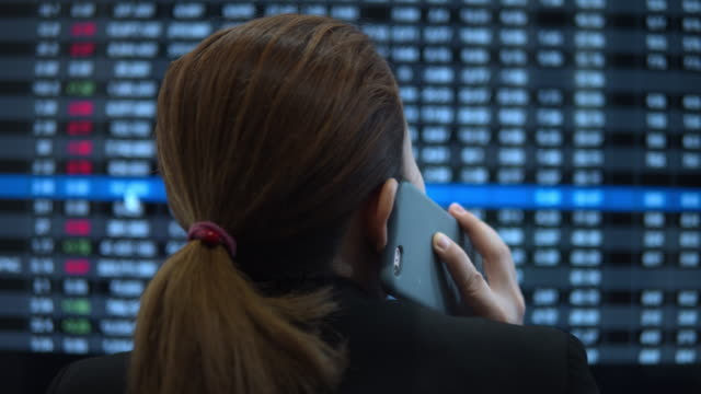 Businesswoman talking on smart phone and looking stock market financial screen