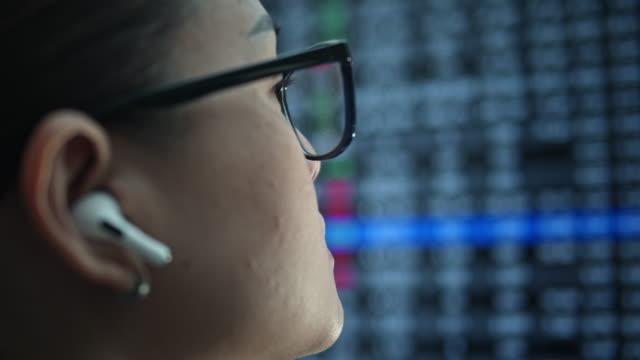 businesswoman talking on smart phone with hands-free device and looking stock market financial screen - słuchawki filmów i materiałów b-roll