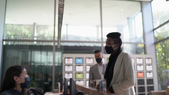 Businesswoman talking to receptionist on entrance of office's lobby - with face mask