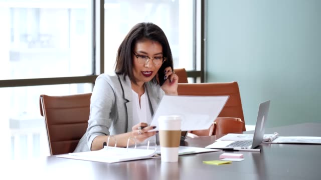 Businesswoman talks with colleague while reviewing paperwork