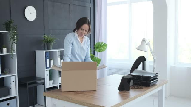 vídeos y material grabado en eventos de stock de empresaria unboxing pertenencias en nueva oficina - principios
