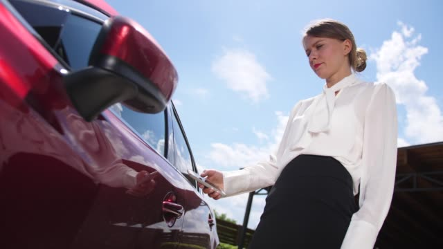 Businesswoman unlocking car using smartphone app Close-up of attractive female in business clothes using modern technology to unlock car doors holding cellphone with special application. Formally dressed businesswoman opening door and getting in car bluetooth stock videos & royalty-free footage
