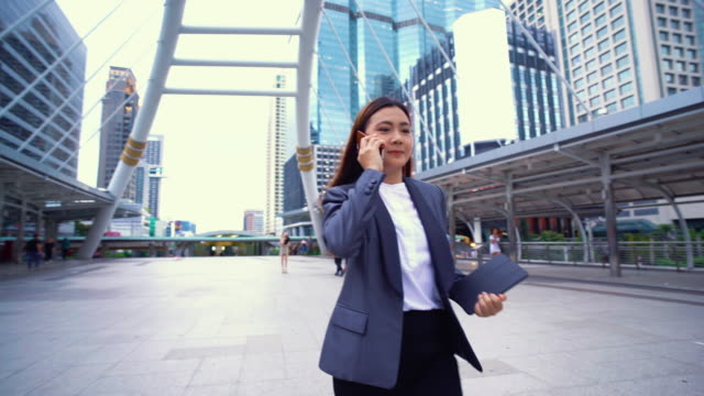 Businesswoman use a phone in a city,Tracking shot video