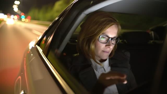 vídeos de stock, filmes e b-roll de ms businesswoman usando um tablet digital durante a condução para o aeroporto - carro mulher