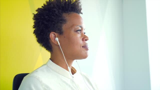 vidéos et rushes de femme d'affaires à l'aide d'une paire d'écouteurs. - podcasting