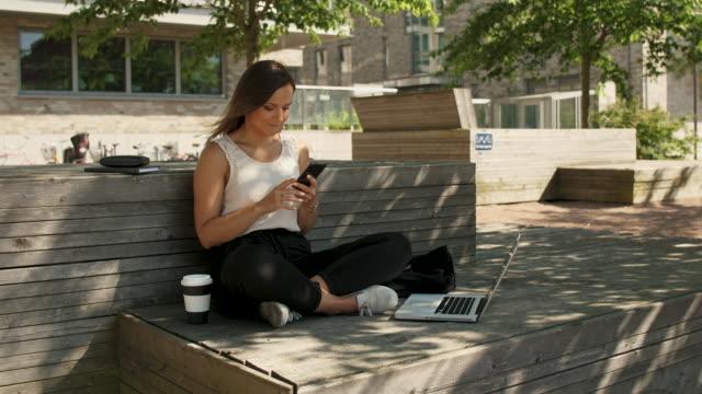 imprenditrice che usa uno smartphone - ambientazione esterna video stock e b–roll