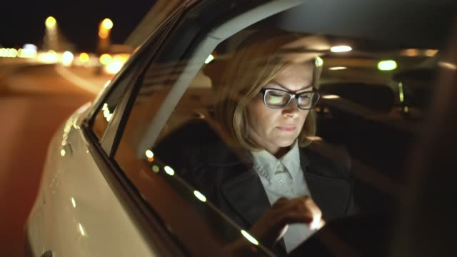 MS Businesswoman using a tablet on the back seat of a taxi driving at night
