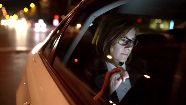 MS Businesswoman using a tablet on the back seat of a taxi video