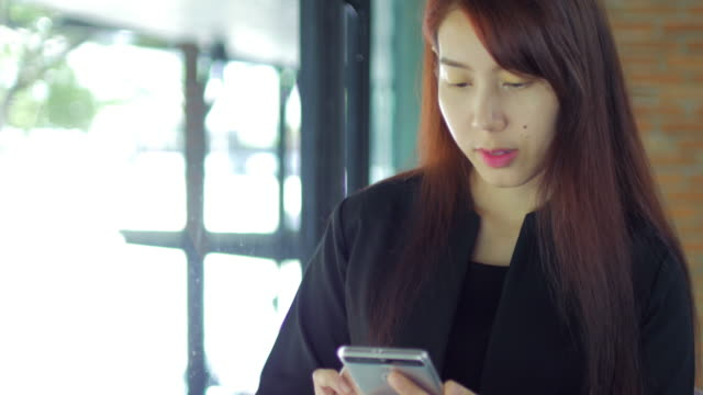 Businesswoman using and touching smartphone in her office , dolly shot left to right video