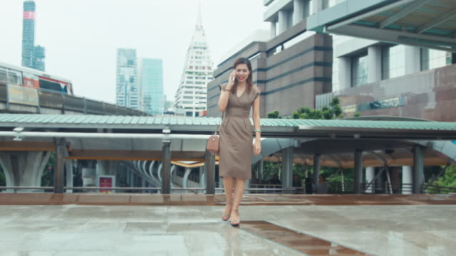 Businesswoman using cell phone at Bangkok downtown video