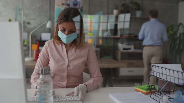 Businesswoman using computer in bank office Woman sitting at desk with sneeze guard on it and using computer in bank office, she's wearing protective face mask and surgical gloves for protection against virus during covid-19 pandemic covid mask stock videos & royalty-free footage