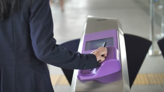 vídeos de stock, filmes e b-roll de mulher de negócios usando o pagamento contactless na estação de trem - pagando