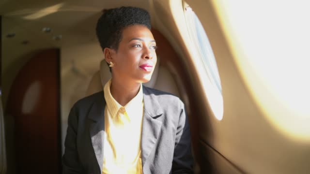 businesswoman using digital tablet and looking through corporate jet window - guardare il paesaggio video stock e b–roll
