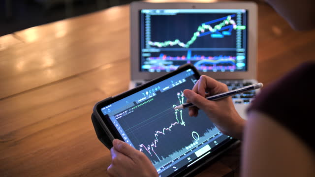 businesswoman using digital tablet for stock market data analyzing in trading - professione finanziaria video stock e b–roll