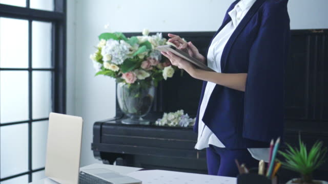 businesswoman using digital tablet in her office,slow motion - owner laptop smartphone video stock e b–roll