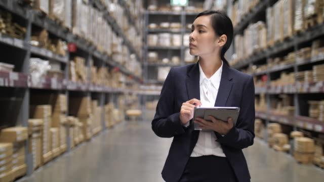 vídeos y material grabado en eventos de stock de mujer empresaria que usa la tableta digital en el almacén - 20 a 29 años