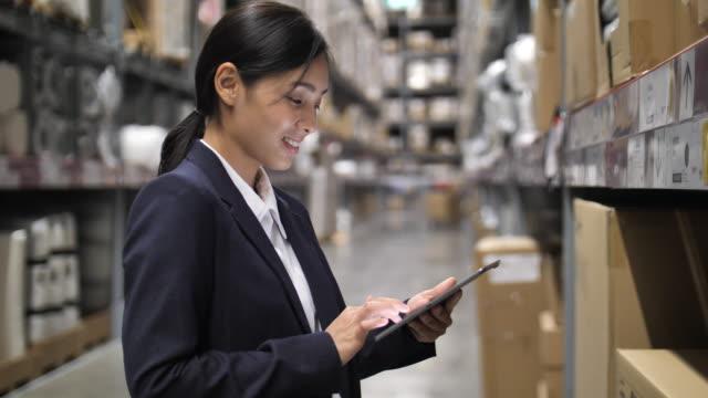 depoda dijital tablet kullanan iş kadını - el aleti stok videoları ve detay görüntü çekimi