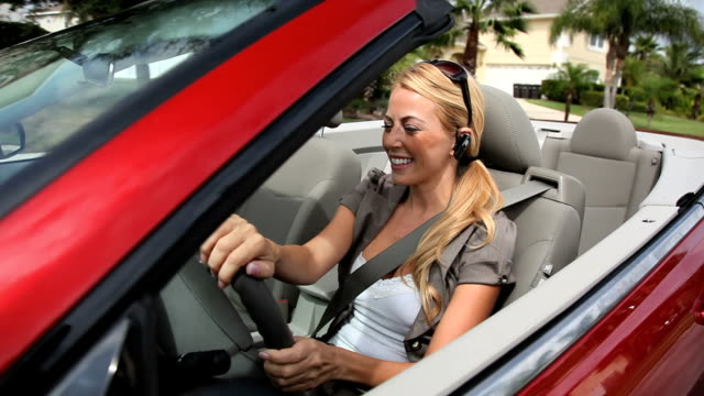 Businesswoman using hands-free communication technology Successful young businesswoman using hands-free communication technology while driving her luxury car bluetooth stock videos & royalty-free footage