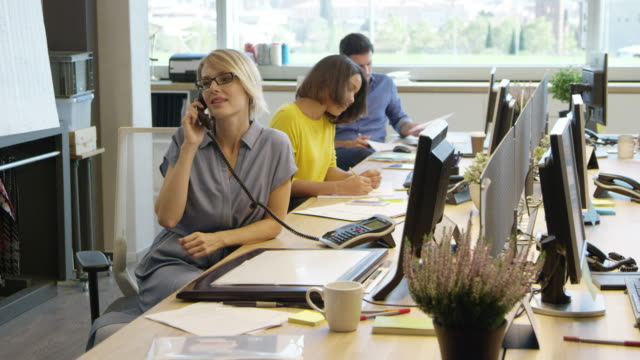 Businesswoman using landline phone by coworkers Dolly shot of mid adult businesswoman using landline phone at table. Male and female professionals are working in office. They are wearing smart casuals. landline phone stock videos & royalty-free footage