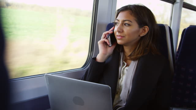 businesswoman using laptop and phone on train shot on r3d - train stock videos and b-roll footage